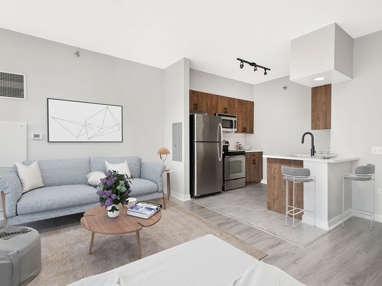 Studio living, dining, kitchen with stainless steel appliances, and queen bed