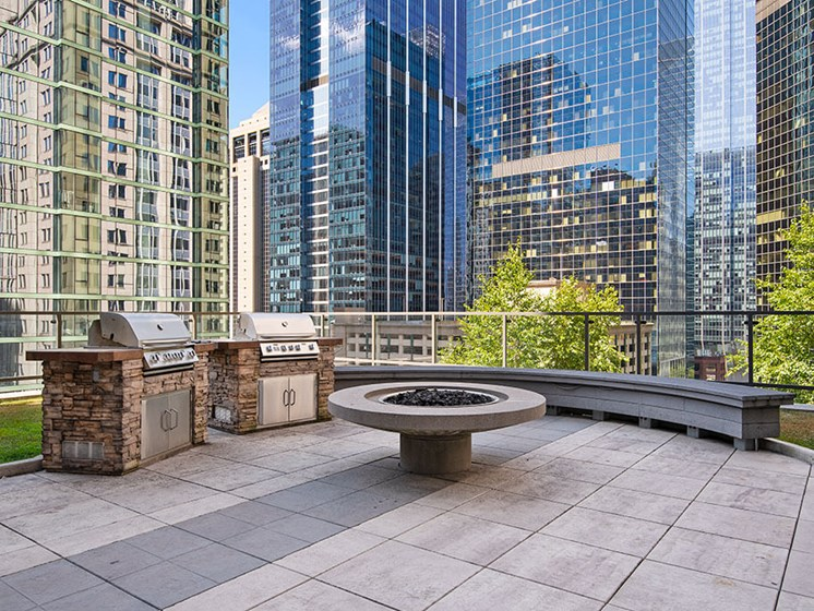 Rooftop outdoor grilling stations with a fire pit and city views