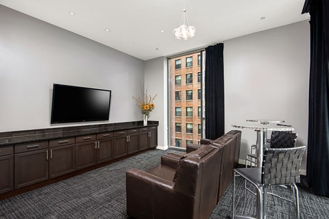 Resident business center with lounge areas, a flat-screen TV and floor-to-ceiling window