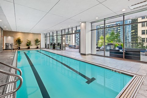 Indoor lap swimming pool with floor-to-ceiling windows and skyline city views