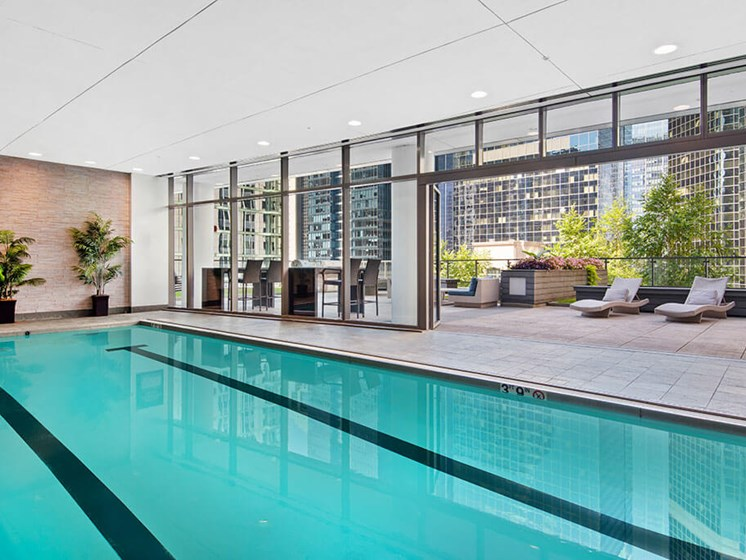 Indoor lap swimming pool with floor-to-ceiling windows, a rooftop patio with lounge areas and a city view