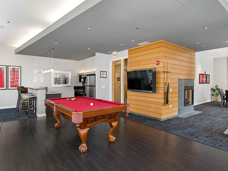 Resident media and game lounge with a pool table and fireplace
