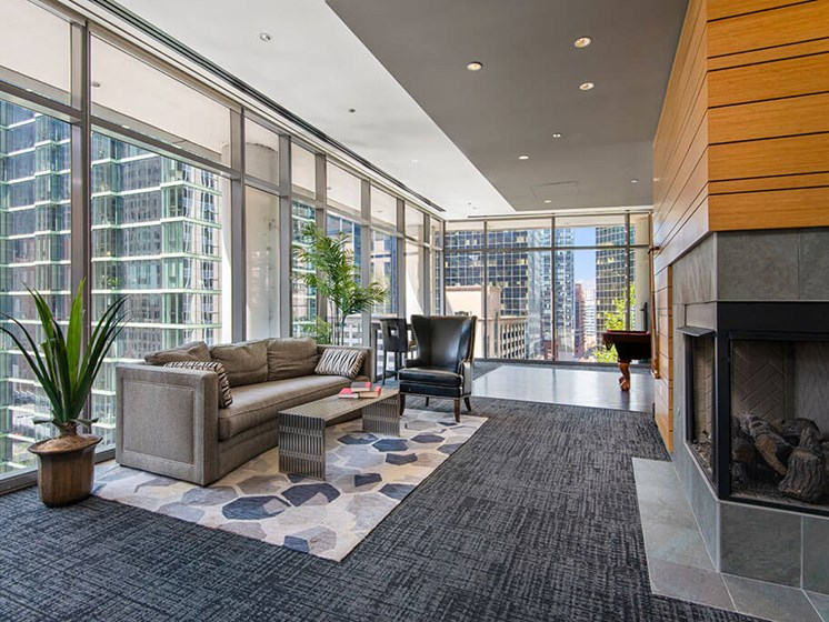 Resident lounge with seating areas, floor-to-ceiling windows and a fireplace
