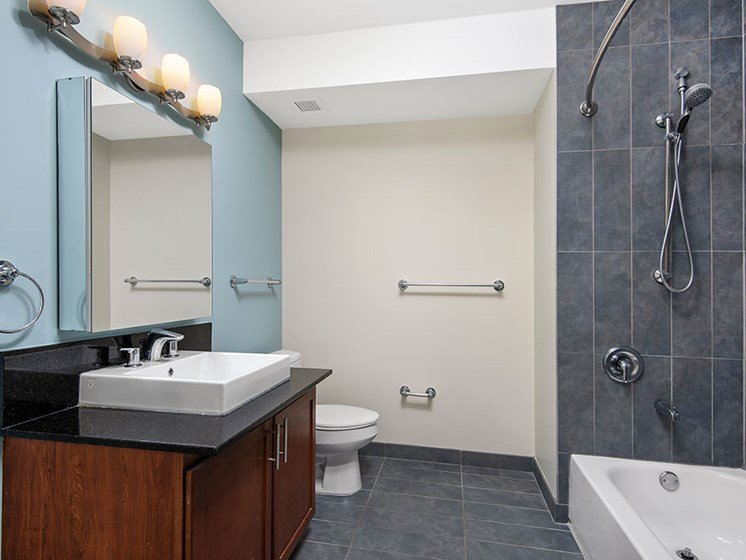 Full model bathroom with granite countertops, cherry cabinetry and a tiled shower with a bathtub