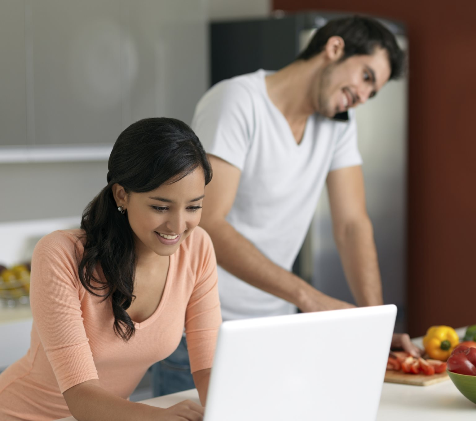 Woman on laptop while man chops vegetables on phone