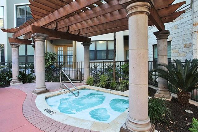 Heated spa under gazebo inside pool courtyard