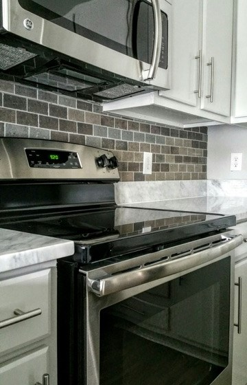 Kitchen with hand-cut tile backsplash, marble countertops, white cabinets and stainless steel appliances