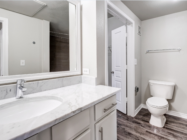 Bathroom with framed mirror, walk-in closet, marble countertop and white cabinets