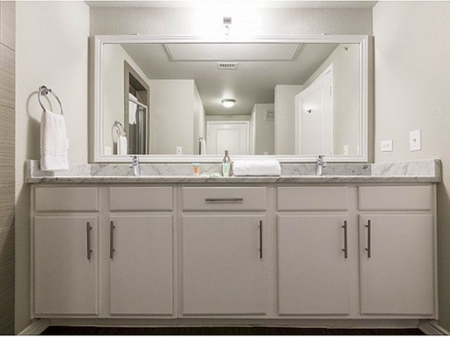 Bathroom with double vanity, marble countertop, and framed mirror