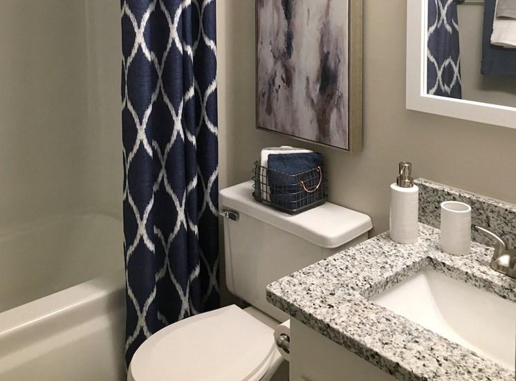 Upgraded bathroom with granite countertops at VUE at Rocket City Apartments