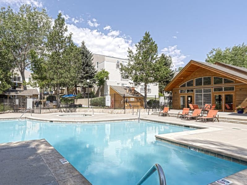 Pool deck with lounge chairs surrounding the pool and the club house in the background.