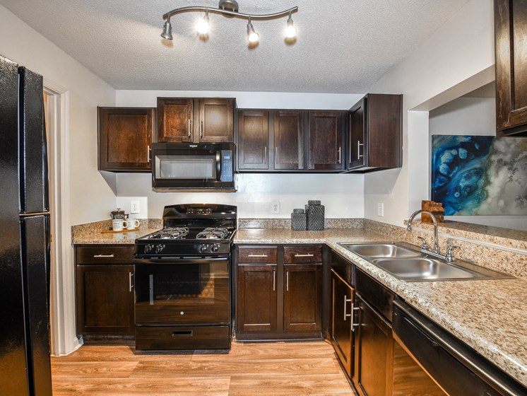 Upgraded kitchen featuring espresso cabinetry at Lakeside at Arbor Place apartment homes in Douglasville, GA  30135