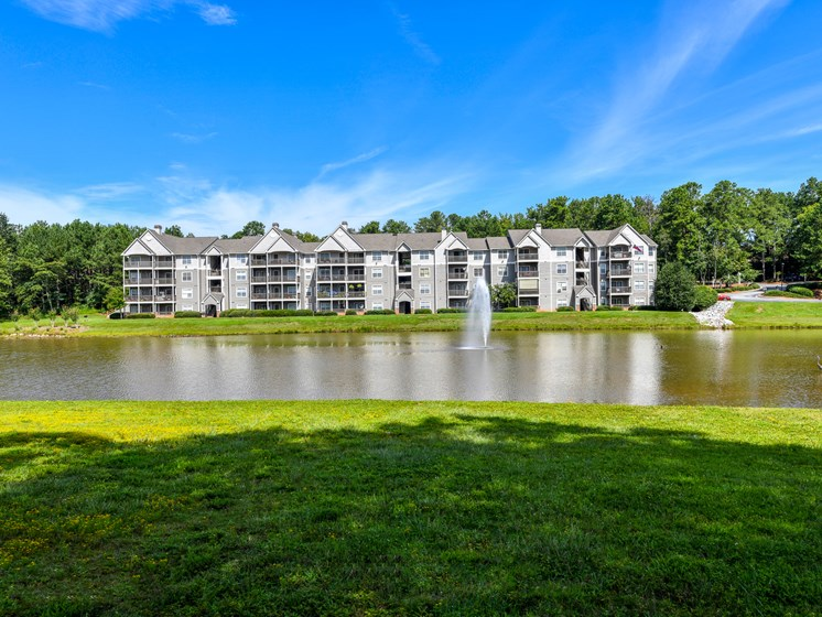 Tranquil green space featuring natural waterscape and fountain at Lakeside at Arbor Place apartment homes in Douglasville, GA 30135