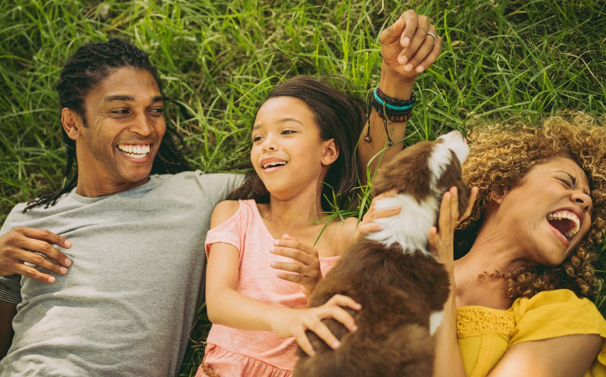Happy family laying in grass with dog