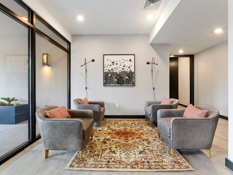 Grey arm chairs surround colorful rug in apartment lounge for residents of The Palmer West