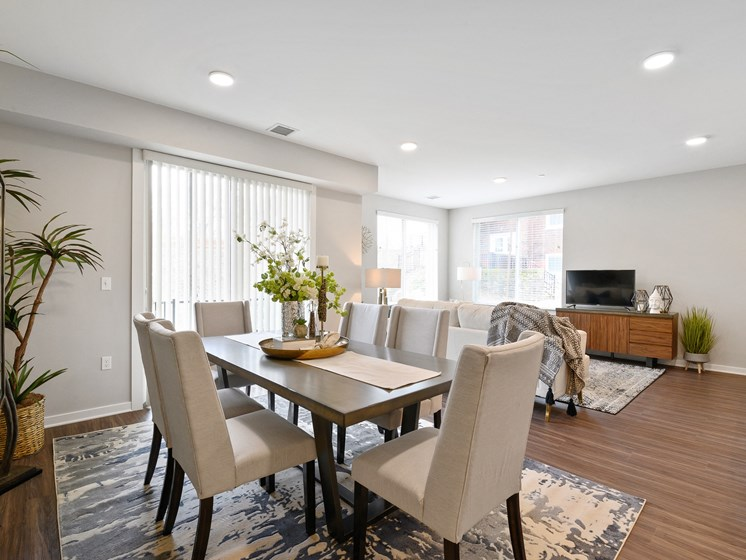 Large dining area with sunny windows, overhead lighting, and vinyl hardwood flooring
