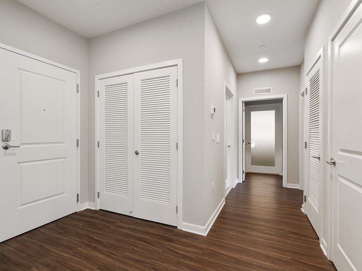 Elegant, modern entryway with lots of closet space and crisp white doors