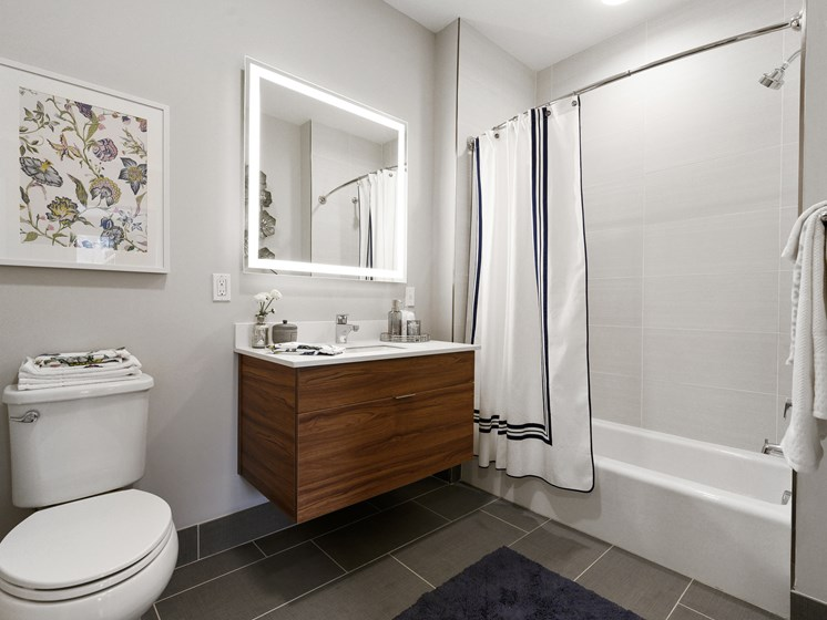 Large modern bathroom with light up mirror over sink and vanity and tiled flooring