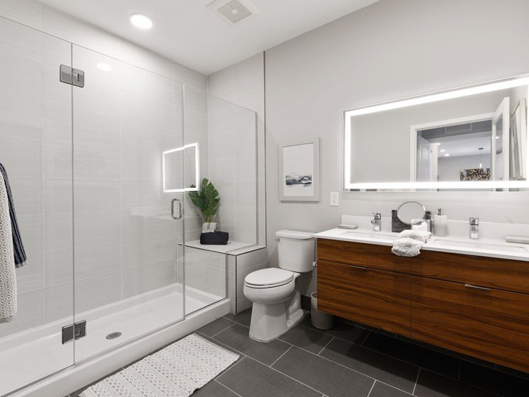 Large bathroom with couple's vanity featuring two sinks and light-up mirror and walk-in shower with bench