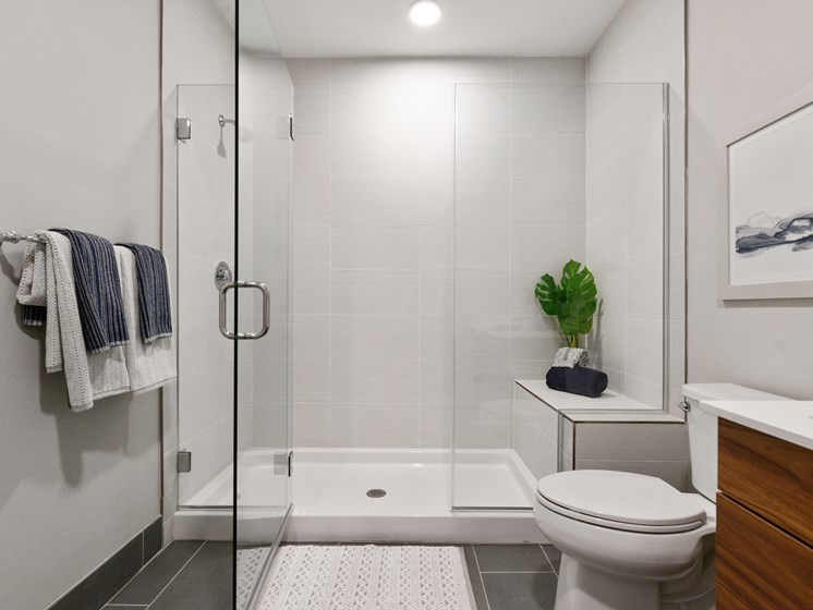 Gorgeous bathroom with huge white, tiled walk-in shower with bench and glass doors