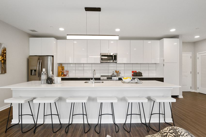 Huge apartment kitchen with white cabinetry, breakfast bar, and stainless steel appliances