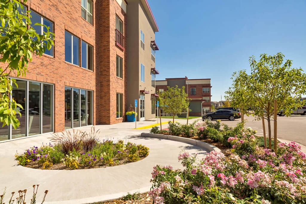 Westwood Green Leasing Office Entrance with round planter, flowers and trees