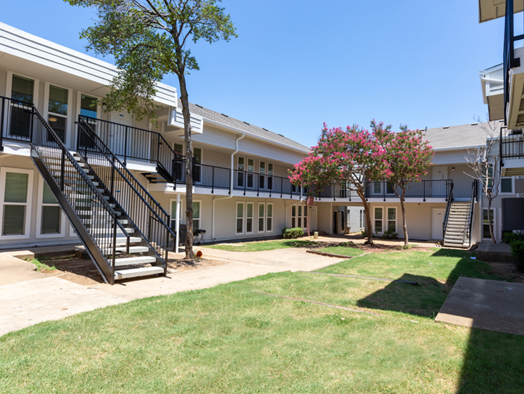 Courtyard area in the middle of apartment buildings-Paddock at Park Row, Arlington, TX