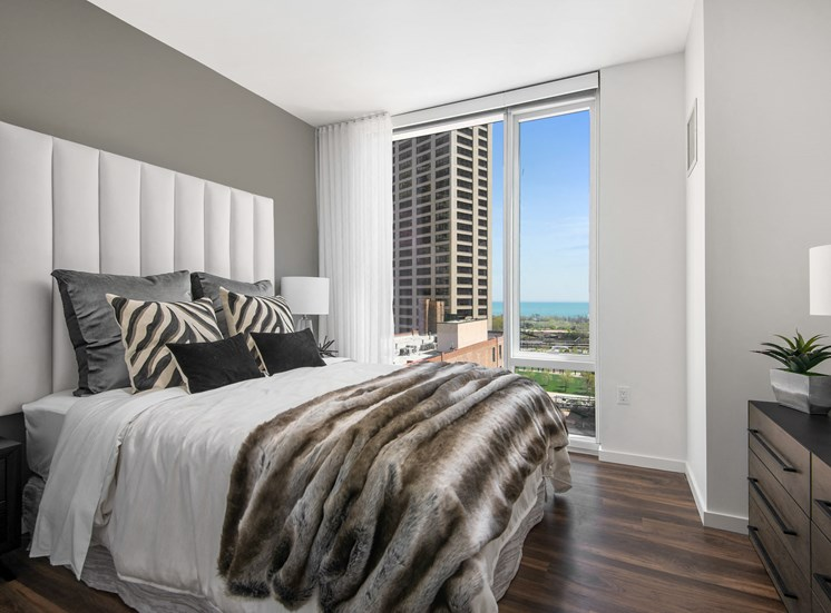 Furnished bedroom with floor to ceiling windows at Eleven40, Chicago