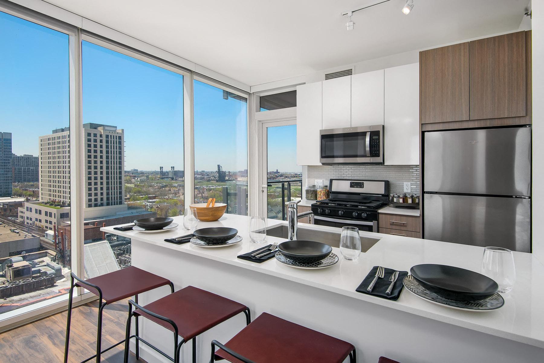 Modern kitchen with white cabinets and quartz kitchen countertops at Eleven40, Illinois