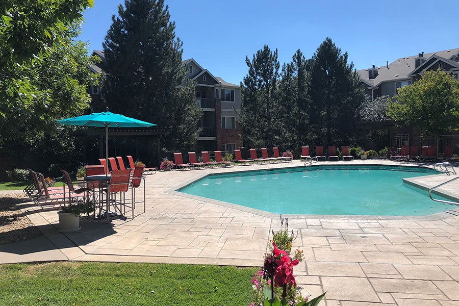 Westlake Greens Pool with orange lounge chairs, turquoise umbrella and grassy area