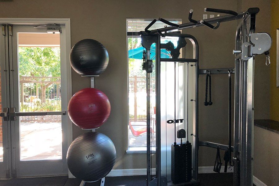 Westlake Greens Fitness Center equipment and bosu balls with glass doors out to the pool
