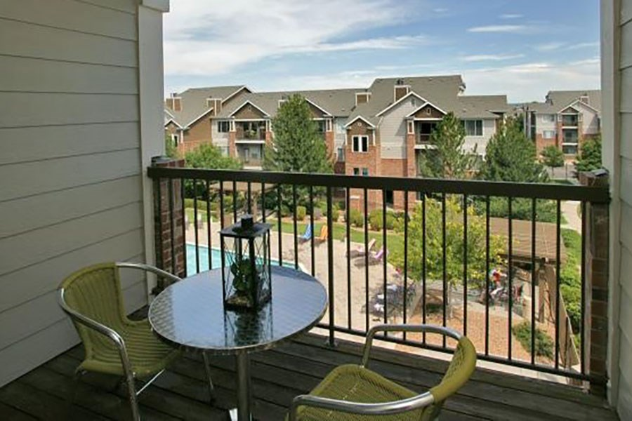Westlake Greens Balcony with green bistro chairs and tables looking out at the pool and other apartment buildings