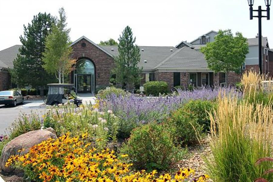 Westlake Greens Leasing Office brick front entrance with yellow flowers and plants in from
