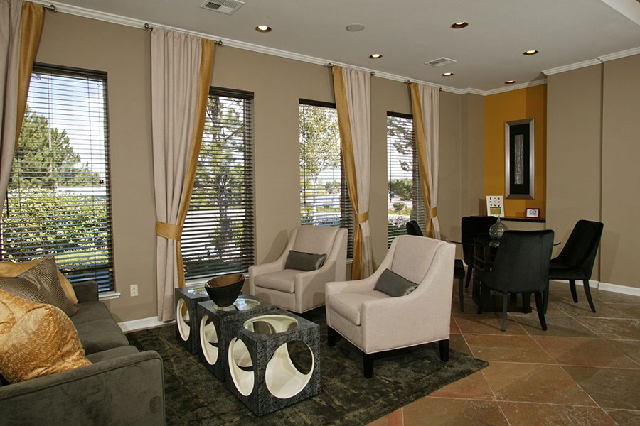 Westlake Greens Clubhouse seating area with black and white chairs, white curtains and windows