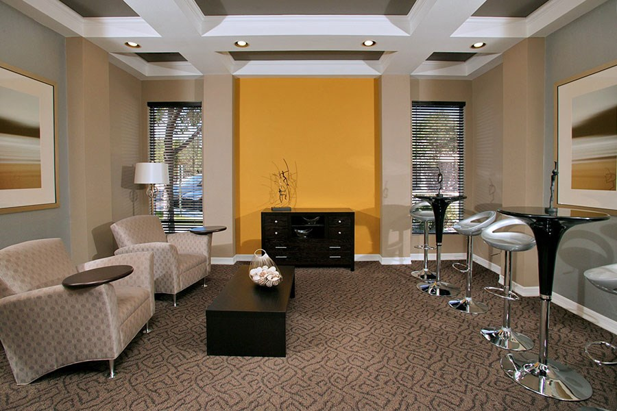 Westlake Greens Clubhouse lounge room with beige chairs and hightop tables