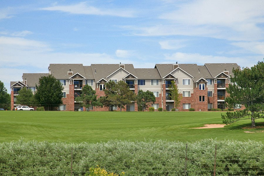 Westlake Greens brick apartment buildings with green grass and trees in front