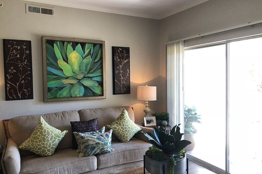 Westlake Greens Living Room with grey couch, and green succulent wall art and sliding glass door to patio
