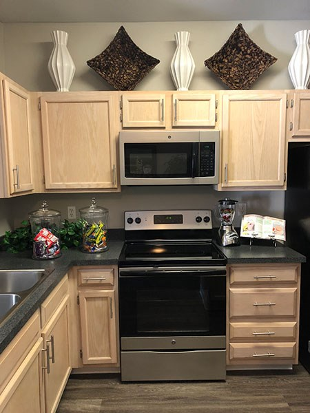 Westlake Greens Kitchen with blonde cabinets, dark counter tops and stainless steel appliances