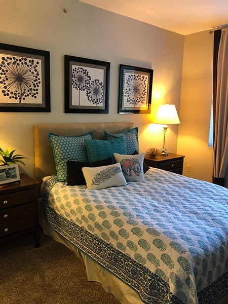 Westlake Greens master bedroom with queen sized bed with green and white bedding and floral art above. beige wall to wall carpet