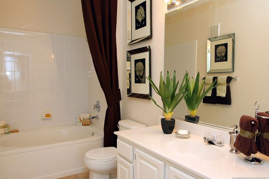 Westlake Greens Bathroom with white cabinets and counter tops, bathtub & shower, and brown shower curtain