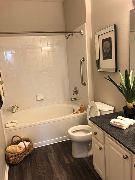 Westlake Greens bathroom, with hardwood-style flooring, white cabinets, dark counter tops, and tub/shower