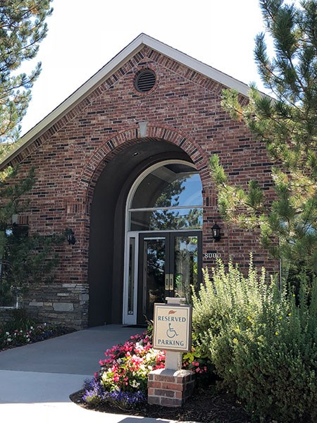Westlake Greens Leasing Office brick front entrance with green plants and flowers