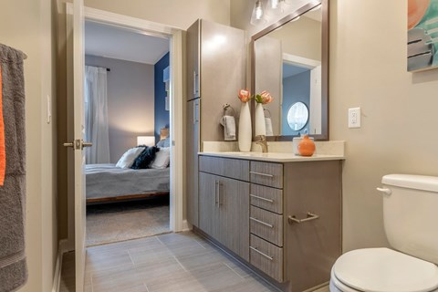 Bathroom with a view of the bedroom, storage under the sink, and decor on walls