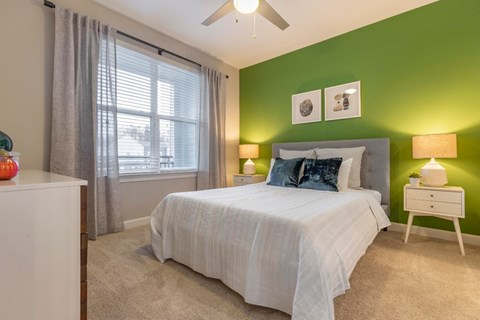 Bedroom with green accent wall, lamps, and bedroom furniture