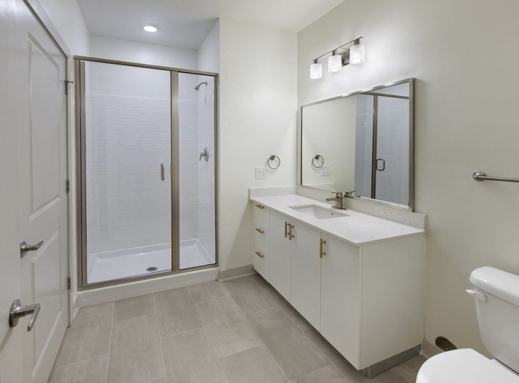 Elegant Tiled Bathroom with Quartz Countertops, Modern Lighting and Walk-In Shower at Park 35 on Clairmont Apartment Homes, 3500 Clairmont Ave. Birmingham, AL 35222