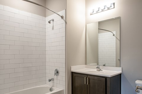 Bathroom with curved shower rod and high-end shower tiling
