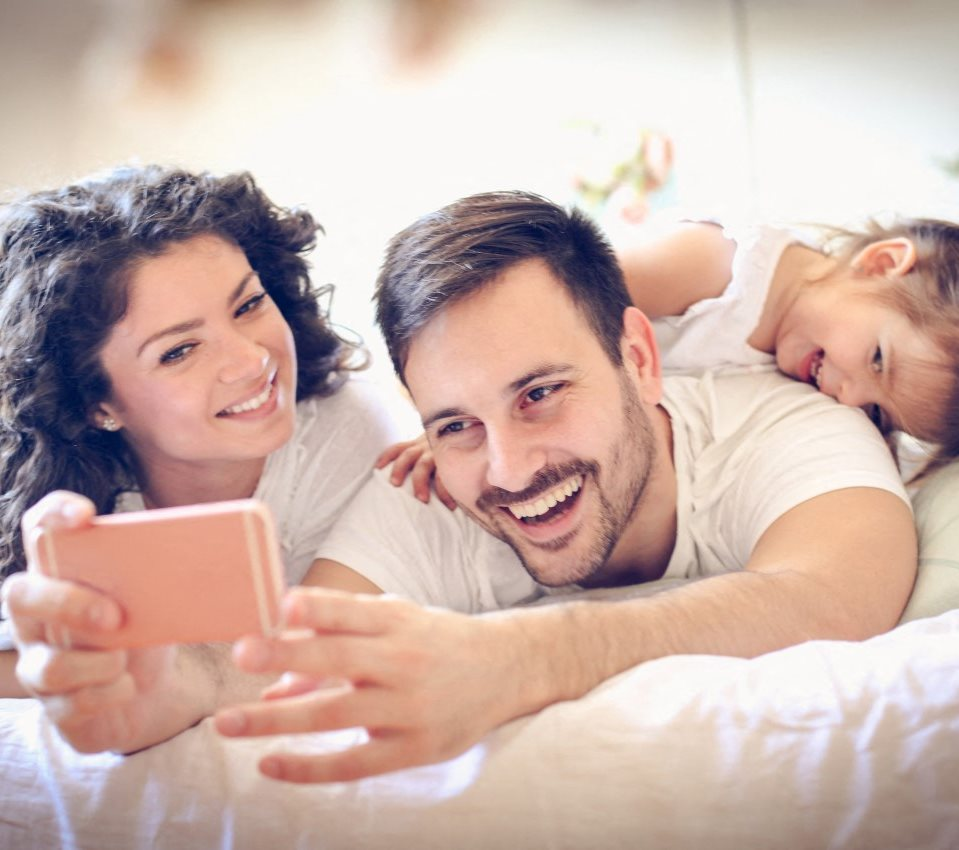 Mother and Father Laying On Bed Taking Selfie With Child