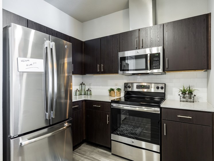 Kitchen with dark cabiets, stainless steel appliances, quartz countertops, and subway tile backsplash