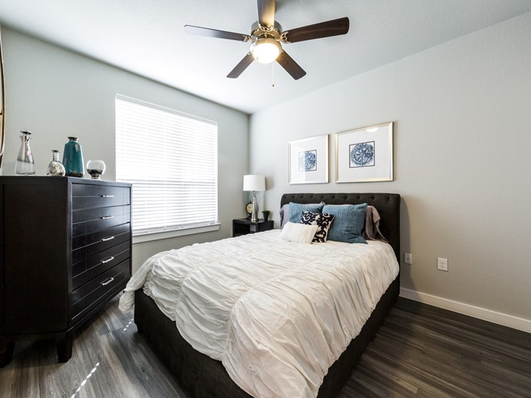 Bedroom one with wood-style flooring, ceiling fan and large bedside window