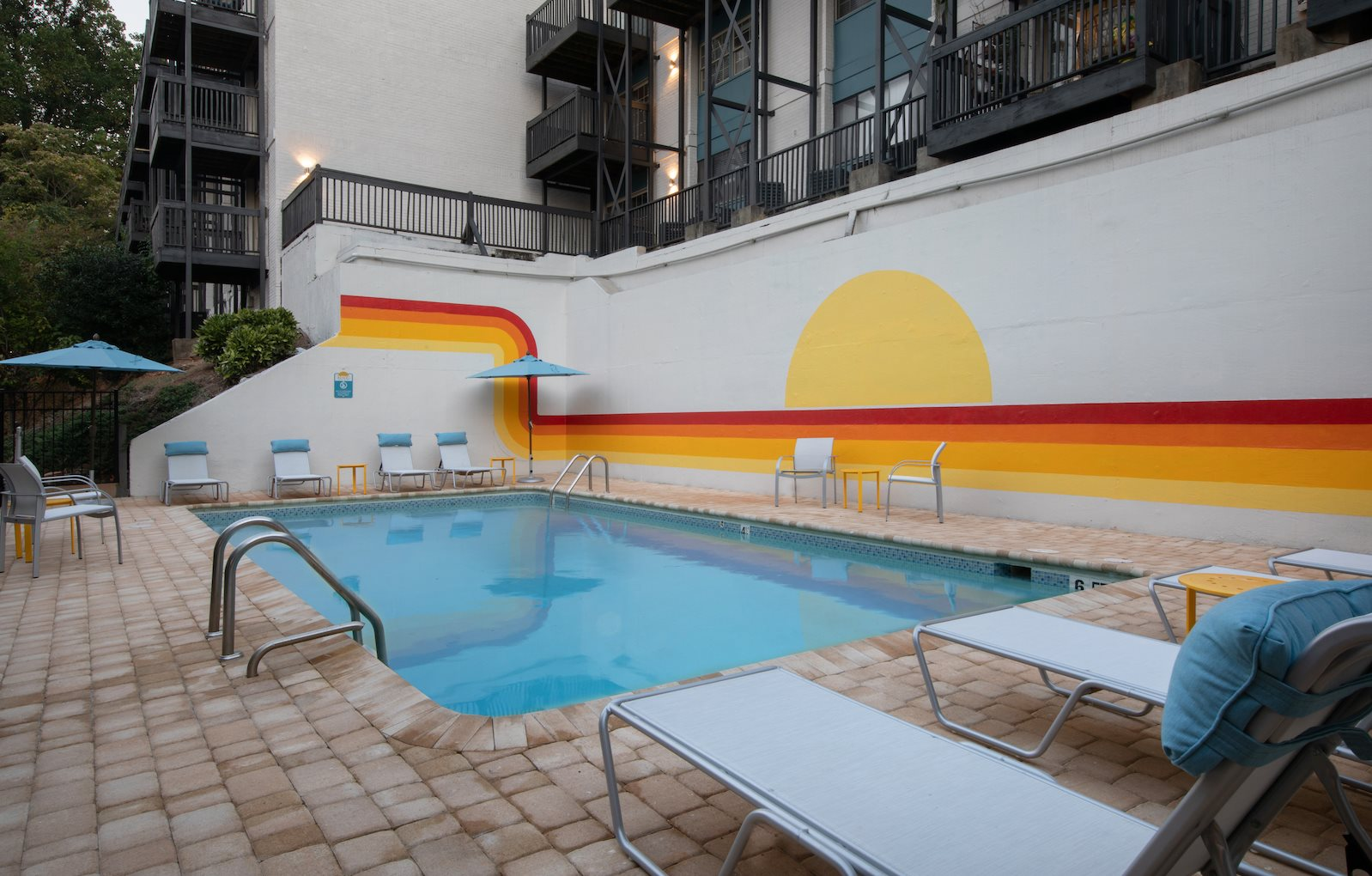 Renovated pool and sundeck with lounge furniture and mural
